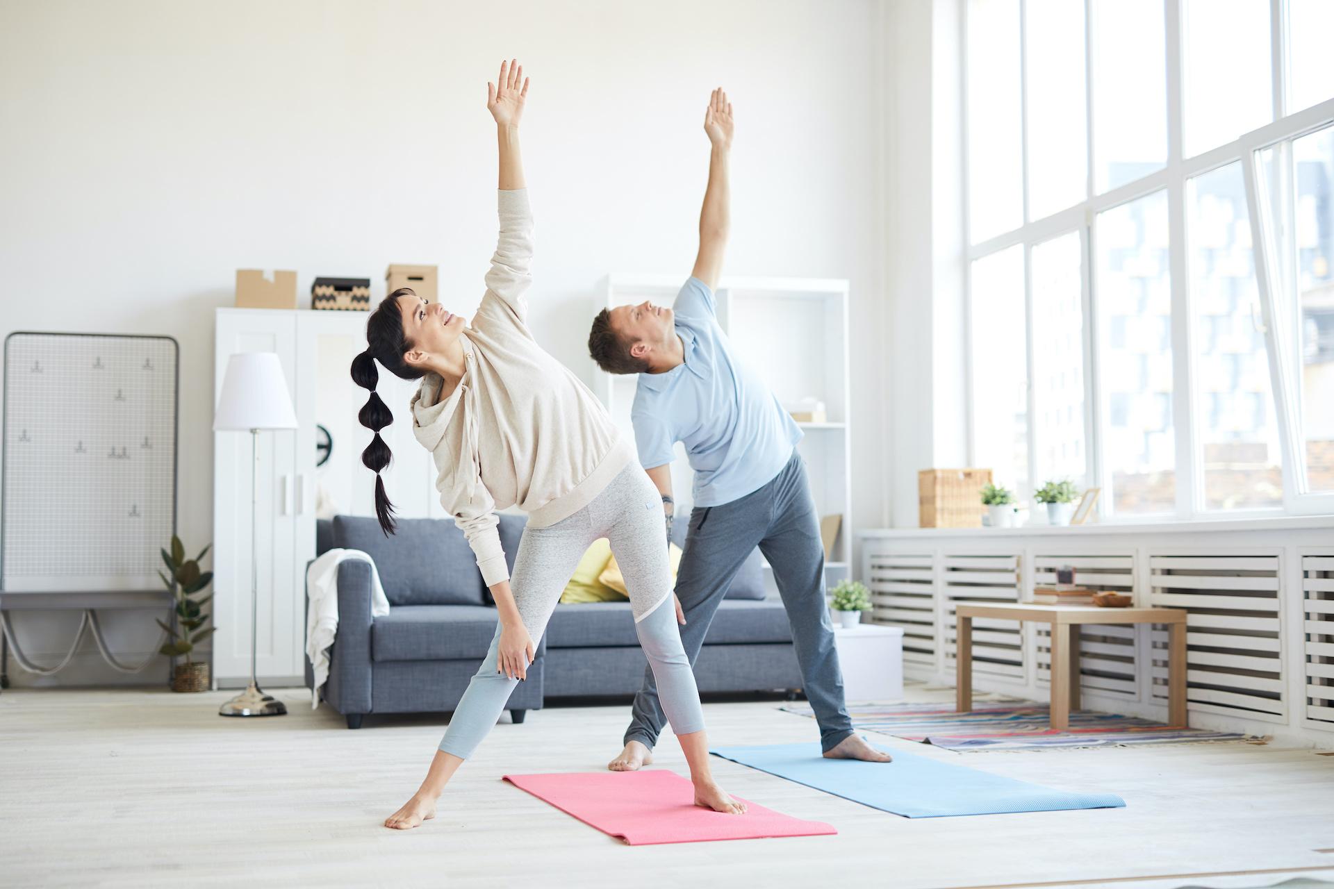 Una mujer y un hombre realizan actividad física en su casa